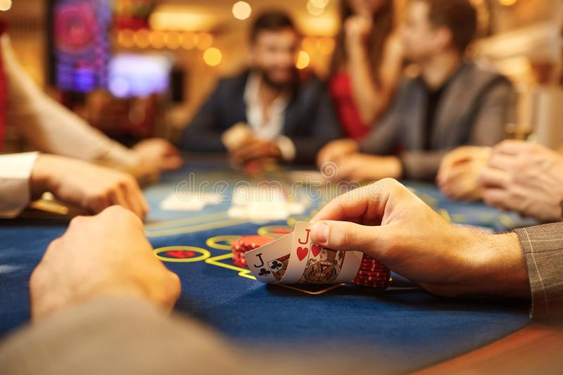 Folket spelar poker på tabellen i kasinot royaltyfri fotografi