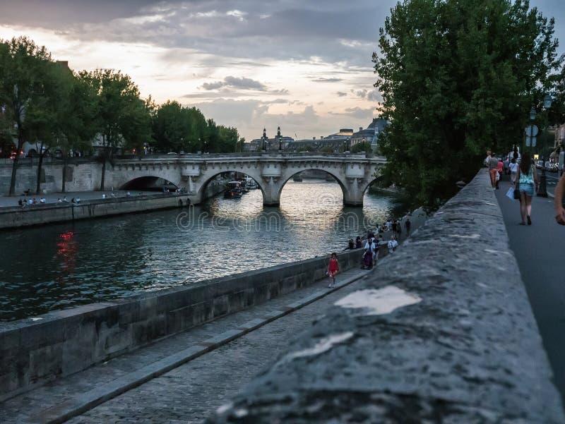 Folket strosar förbi Seinen på en sommarafton i Paris arkivbild