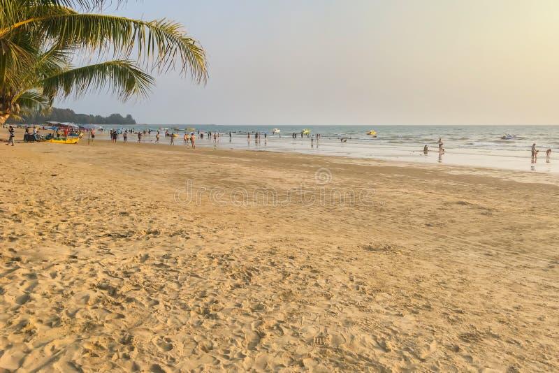 Folket strosar stranden, havet och sanden i aftonen under sommarferierna arkivfoton