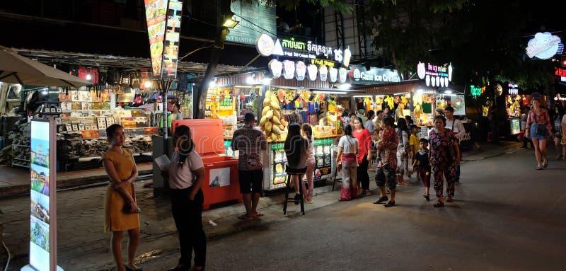 Folket strosar till och med nattmarknaden, frukt stannar royaltyfria foton