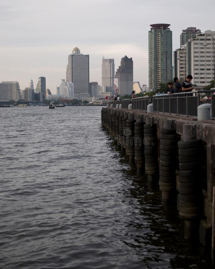 Folket tycker om en tyst tid på en pir på Chaoet Praya River i Bangkok, Thailand, med moderna byggnader i bakgrunden fotografering för bildbyråer