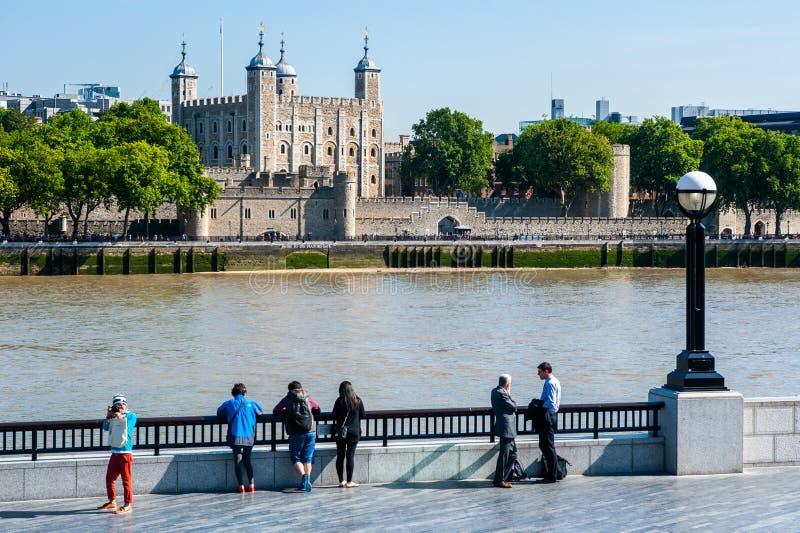 Folket tycker om sikten på tornet av London och flodThemsen i London, UK royaltyfria foton