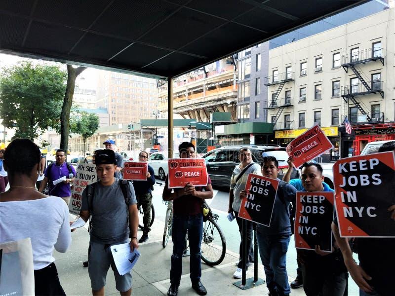 Folket utanför B&H-fotolager i Manhattan med tecken håller jobb i NYC i händerna som protesterar med facklig service royaltyfri foto