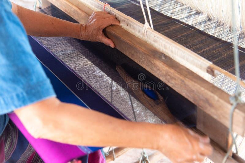 Folket väver med traditionella thailändska Lanna väva maskiner royaltyfri fotografi