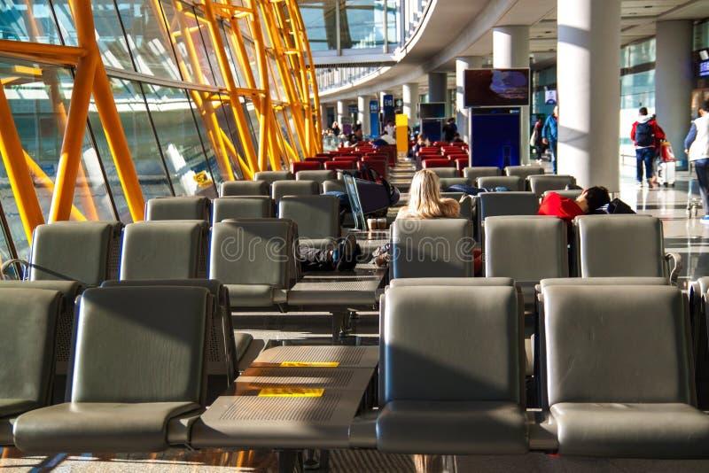 Folket vilar i den väntande vardagsrummet av flygplatsen arkivbild