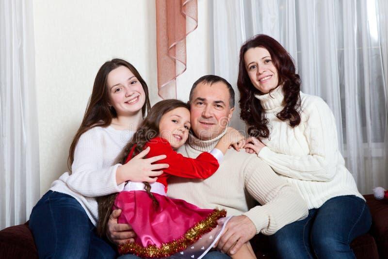 Folkfamilj, jul och adoptionbegrepp - lycklig moder, fader och barn som hemma kramar nära en julgran royaltyfria bilder