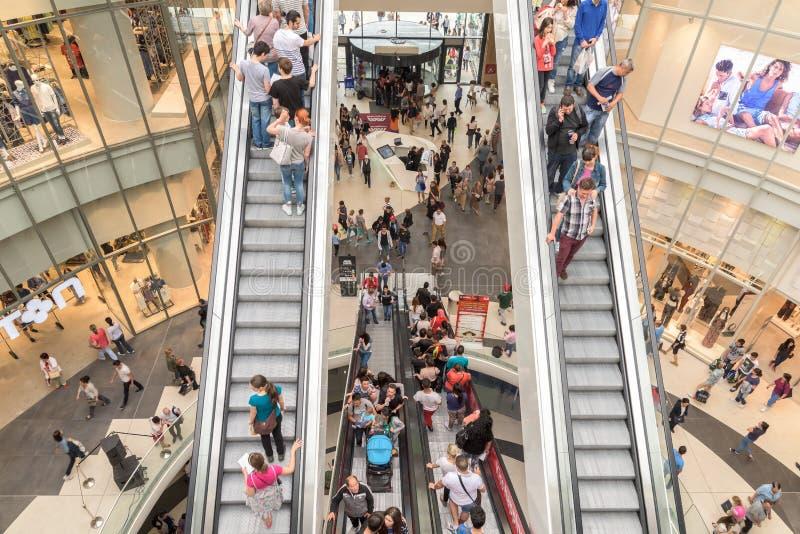Folkfolkmassan rusar i för galleriainre för shopping lyxig trappa royaltyfria foton