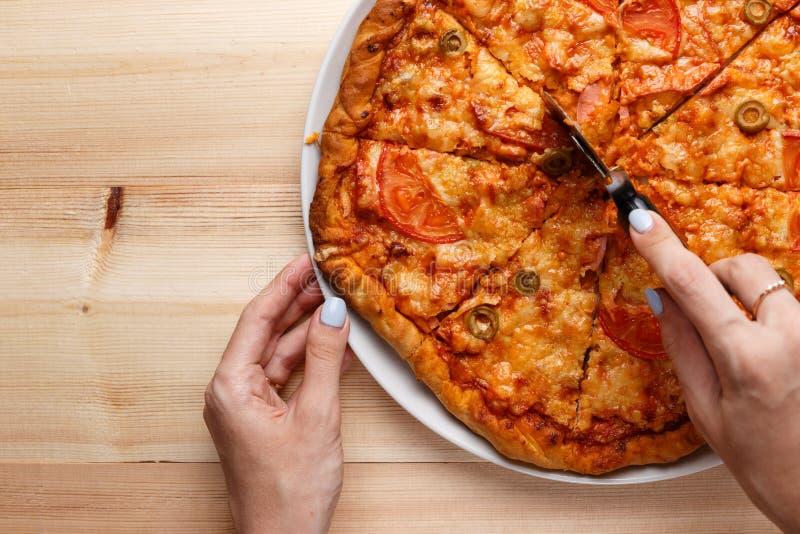 Folkhänder som klipper hemlagad pizza Bästa sikt av en hand som skivar en hemlagad pizza med en skärare arkivbilder