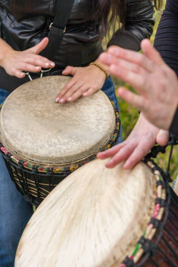Folkhänder som spelar musik på djembevalsar royaltyfria bilder