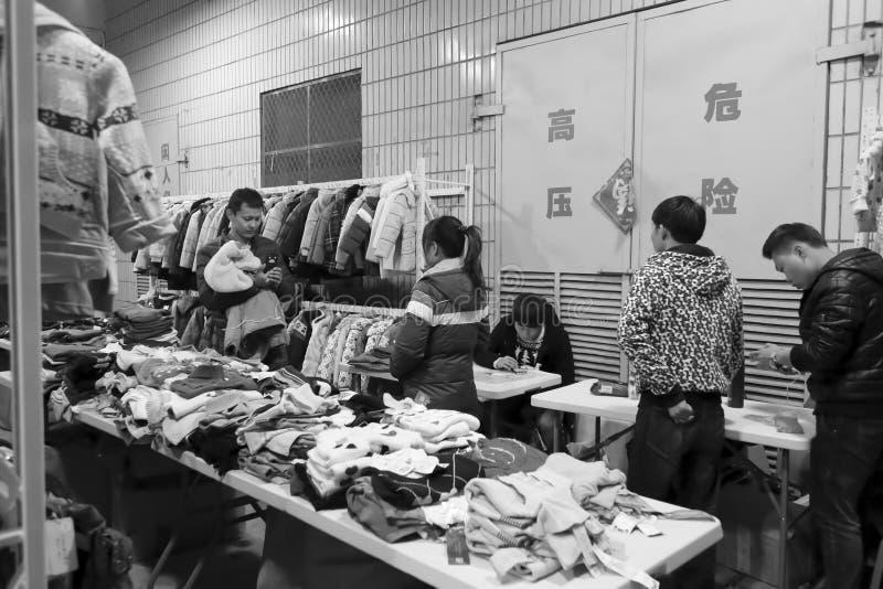 Folkköpkläder i en nattmarknad royaltyfri bild