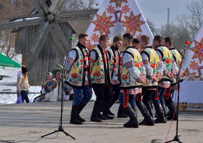 Folklorów mężczyzn wspólnych perfoms krajowy taniec podczas etnicznego festiwalu kolędy w na otwartym powietrzu muzeum, Ukraina obraz royalty free