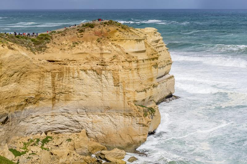 Folkmassa av besökare på klippan framme av de tolv apostlarna på en solig blåsig dag, stor havväg, Australien royaltyfria foton