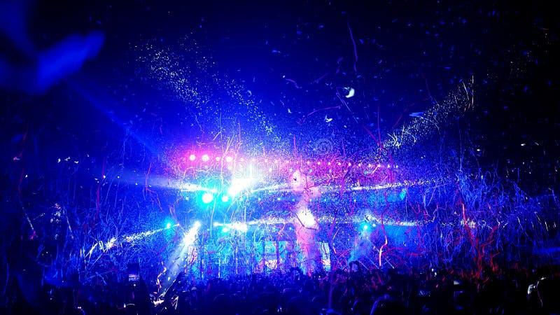 Folkmassa av folk som duschas i banderoller och konfettier på en vaggakonsert royaltyfria foton