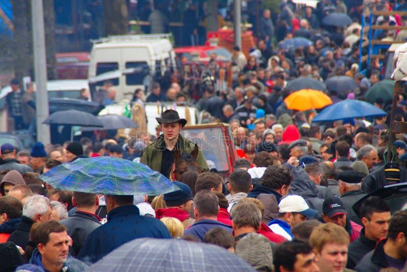 Folkmassa på bymässa på regnig dag