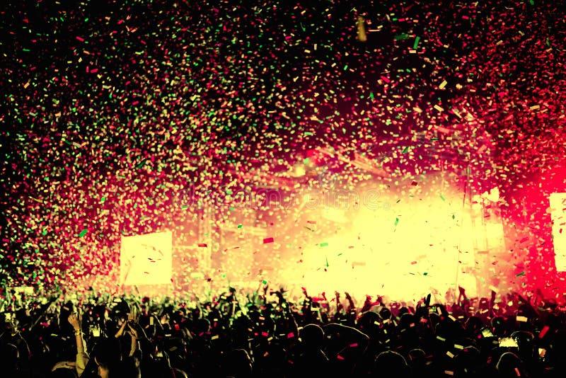 Folkmassa som är främst av ljusa etappljus och konfettier på en musikfe arkivbilder