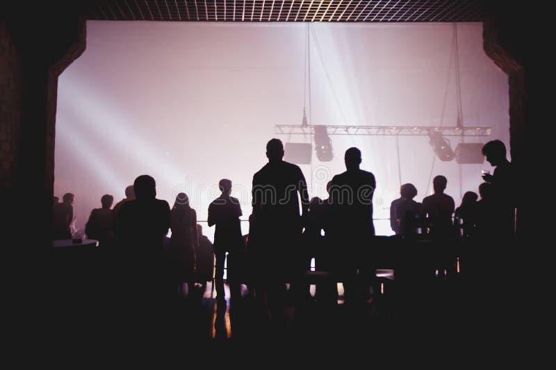 Folkmassa som hurrar och håller ögonen på en musikband på etapp arkivbild