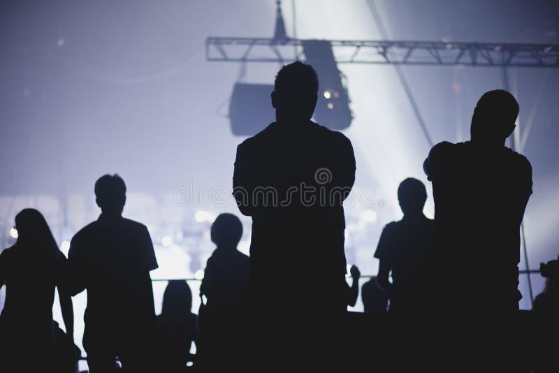 Folkmassa som hurrar och håller ögonen på en musikband på etapp arkivfoton