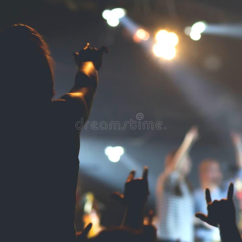 Folkmassa som hurrar och håller ögonen på en musikband på etapp royaltyfria foton