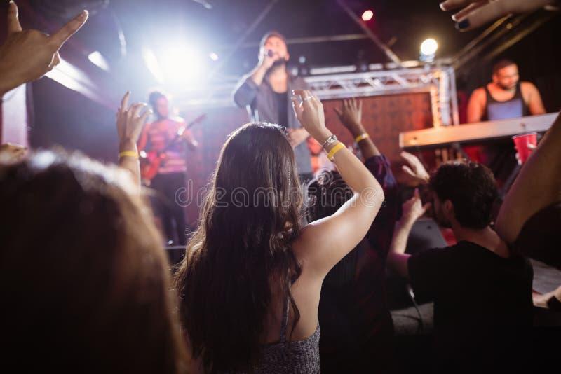 Folkmassa som tycker om konsert för populär musik på nattklubben royaltyfri foto