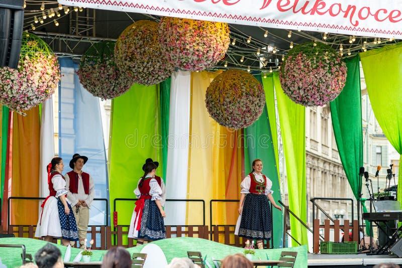 Folkmassaklockaskolbarn att utföra på etapp under berömmar för Pragues påskmarknad i den gamla stadfyrkanten royaltyfri foto