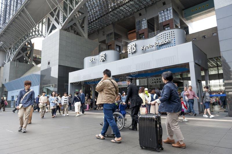Folkmassan av folk på den huvudsakliga ingången till Kyoto posterar byggnad, den viktiga järnvägsstationen och trans.navet i Kyot arkivfoton