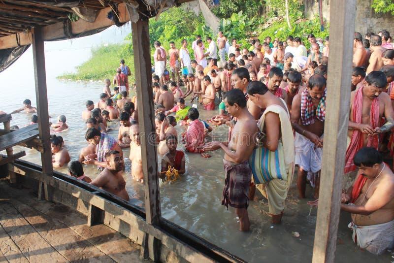 Folkmassan av hinduiskt vallfärdar monterar på packar ihop av floden och ber för sena förfäder royaltyfria bilder