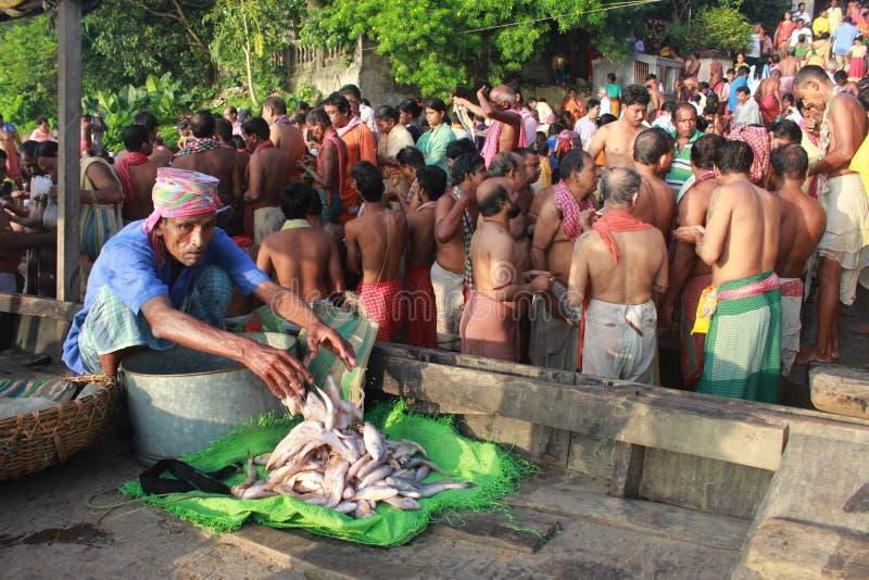 Folkmassan av hinduiskt vallfärdar monterar på packar ihop av floden och ber för sena förfäder royaltyfri foto