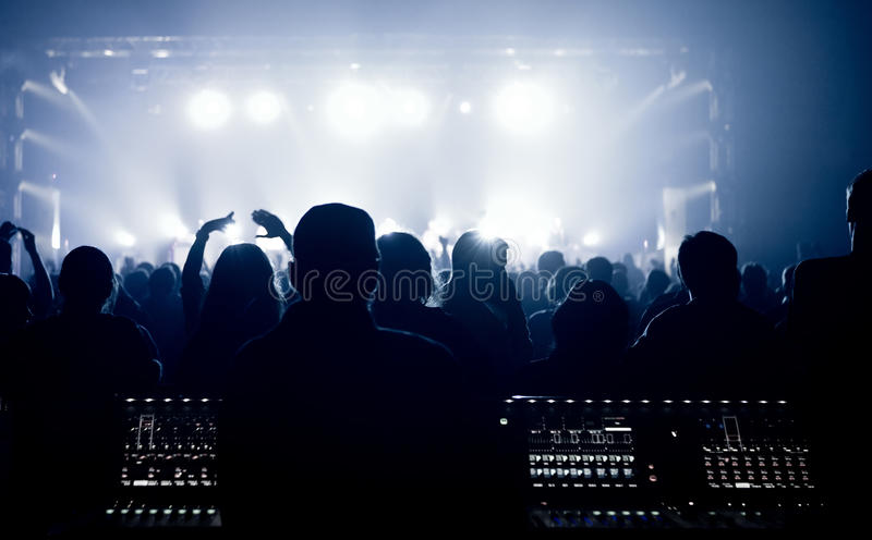 Folkmassan glädjande och hålla ögonen på ett musikband arrangerar på royaltyfria foton