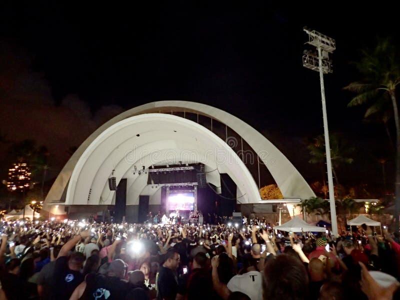 Folkmassan rymmer mobiltelefoner i luften, som Kapena spelar på etapp arkivfoton