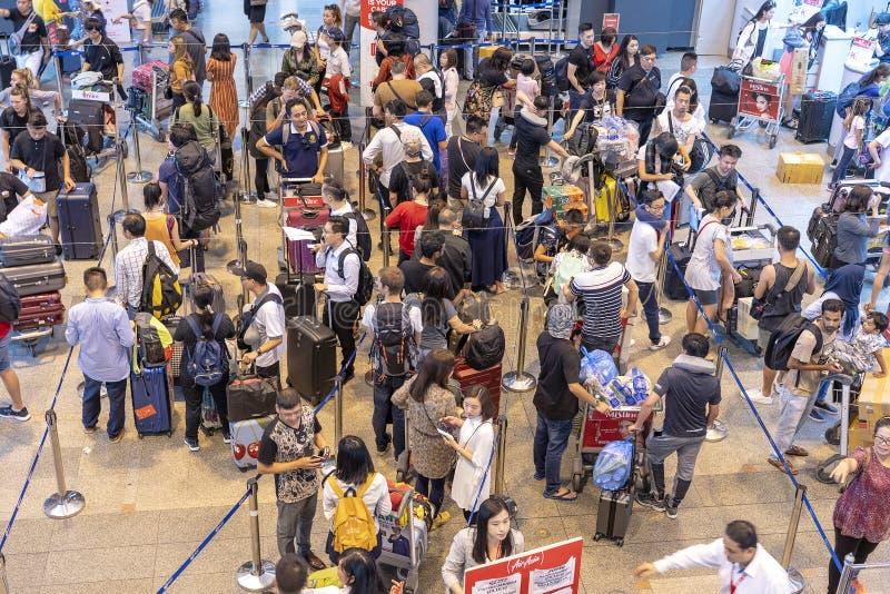 Folkmassapassagerare med bagage i kö på incheckningsdisken på flygplatsen, Thailand royaltyfri bild