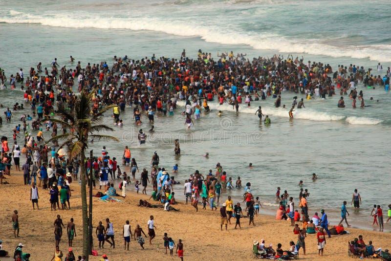 Folkmassor som simmar på stranden i Afrika