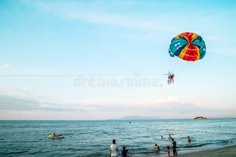 Folkparagliding på stranden över havet arkivfoto