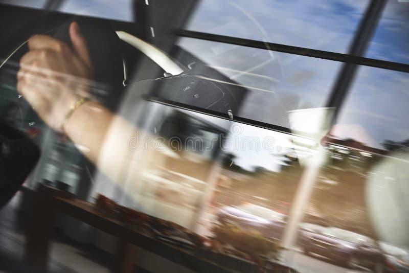 Folkperson som dricker kaffe för pappers- kopp av varmt i hand, medan köra i en bil i morgonen trans. och medel arkivfoto