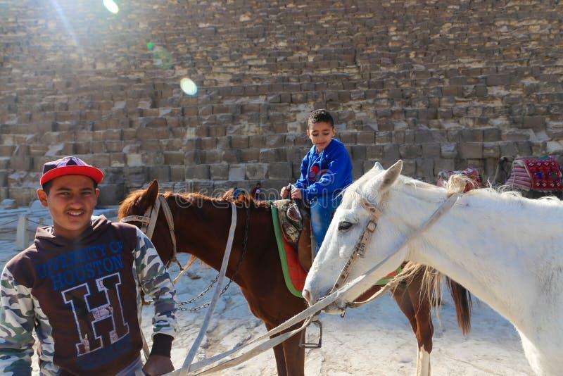 Folkpromenad på hästar på pyramider Egypten fotografering för bildbyråer