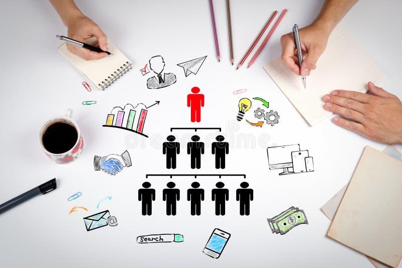 Folkpyramiden med en ledare upptill och konturer jämnar alls, affärsidéen Mötet på den vita kontorstabellen royaltyfri fotografi