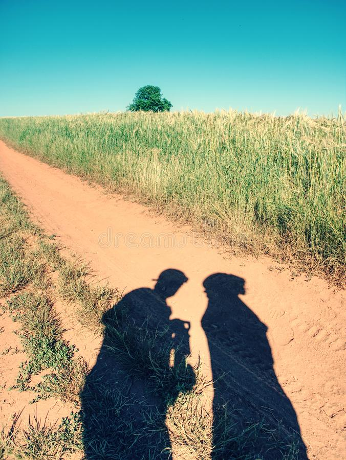 Folkskuggor på den gamla dammiga vägen med ferric röd jord skuggor arkivfoto