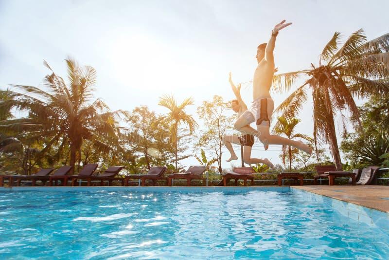 Folkvänner som hoppar till simbassängen, strand semestrar fotografering för bildbyråer