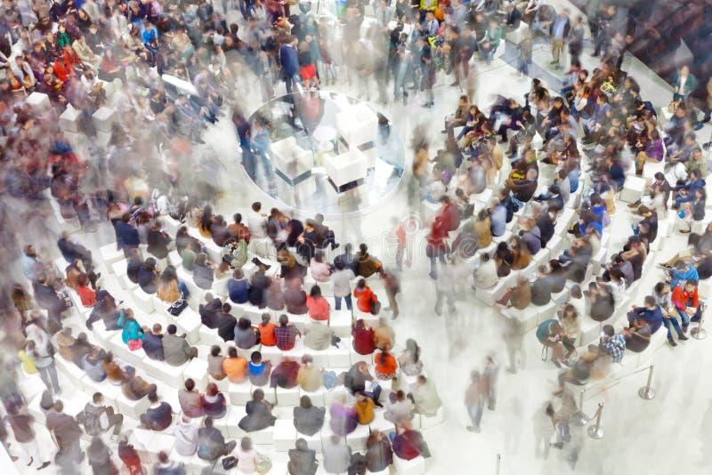 Folla della gente che si siede intorno al punto d'incontro fotografia stock