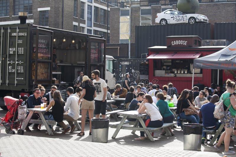 folla eterogenea di Londra orientale che beve una birra fuori del pub fotografie stock