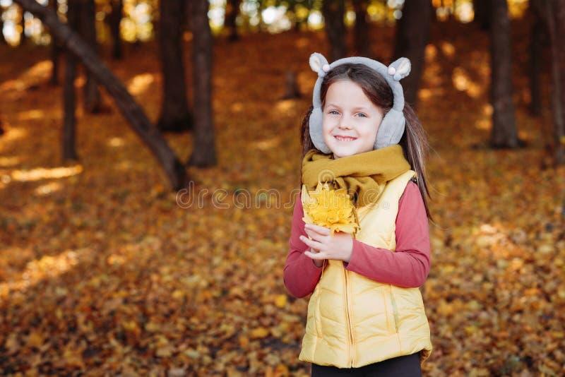 Follaje amarillo de las hojas de arce de la muchacha de la estación del otoño foto de archivo libre de regalías