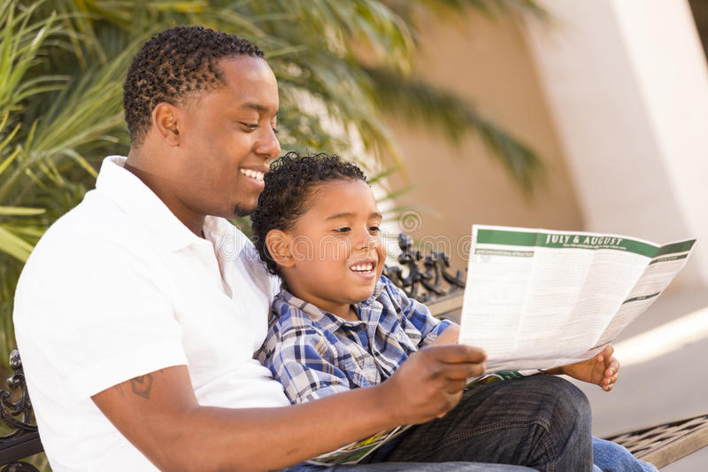 Folleto del parque de la lectura del padre y del hijo de la raza mezclada fotos de archivo libres de regalías