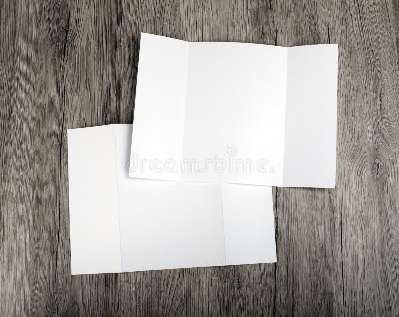 Folleto en blanco del doblez de la puerta sobre fondo de madera imagenes de archivo