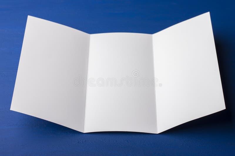 Folleto triple en blanco sobre el fondo azul para substituir su diseño o mensaje imagen de archivo libre de regalías
