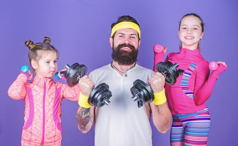 Follow father. Girls cute kids exercising with dumbbells with dad. Motivation and sport example concept. Children repeat. Exercise after dad. Sport exercise for royalty free stock photography