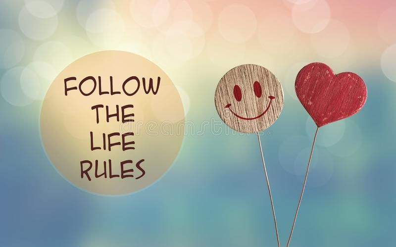 Follow the life rules with heart and smile emoji. Follow the life rules with wooden heart and smile emoji on bokeh light background stock photos