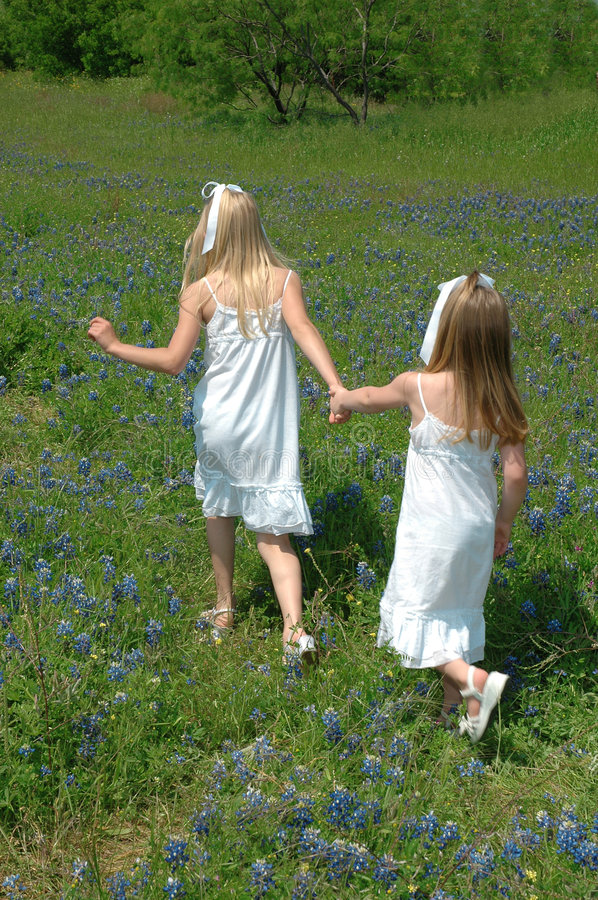 Follow Me. Two sister spending the day in blue bonnet flowers Blue Bonnets are native Texas flowers. The Blue Bonnet is the State Flower of Texas, USA royalty free stock image