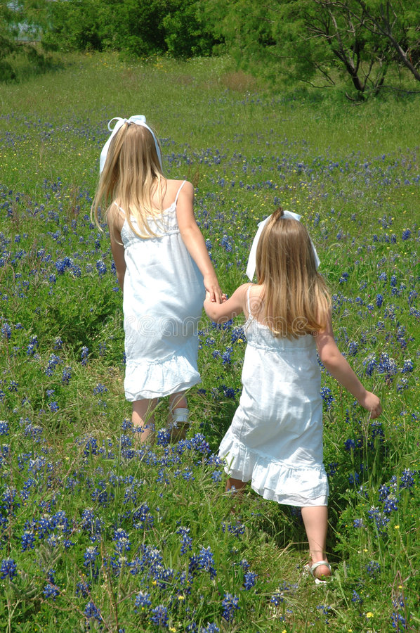 Follow Me. Two sister spending the day in blue bonnet flowers Blue Bonnets are native Texas flowers. The Blue Bonnet is the State Flower of Texas, USA stock photography