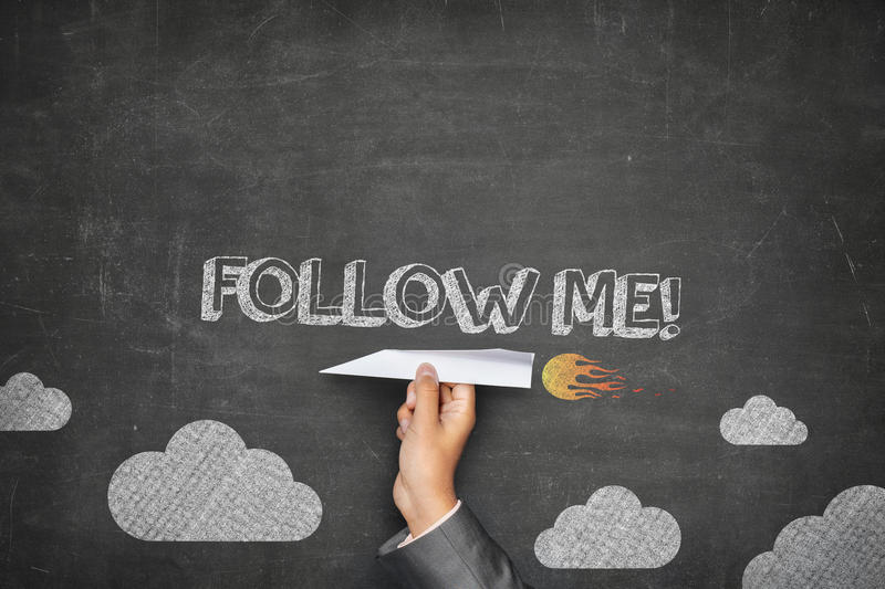 Follow me concept. On black blackboard with businessman hand holding paper plane stock photography