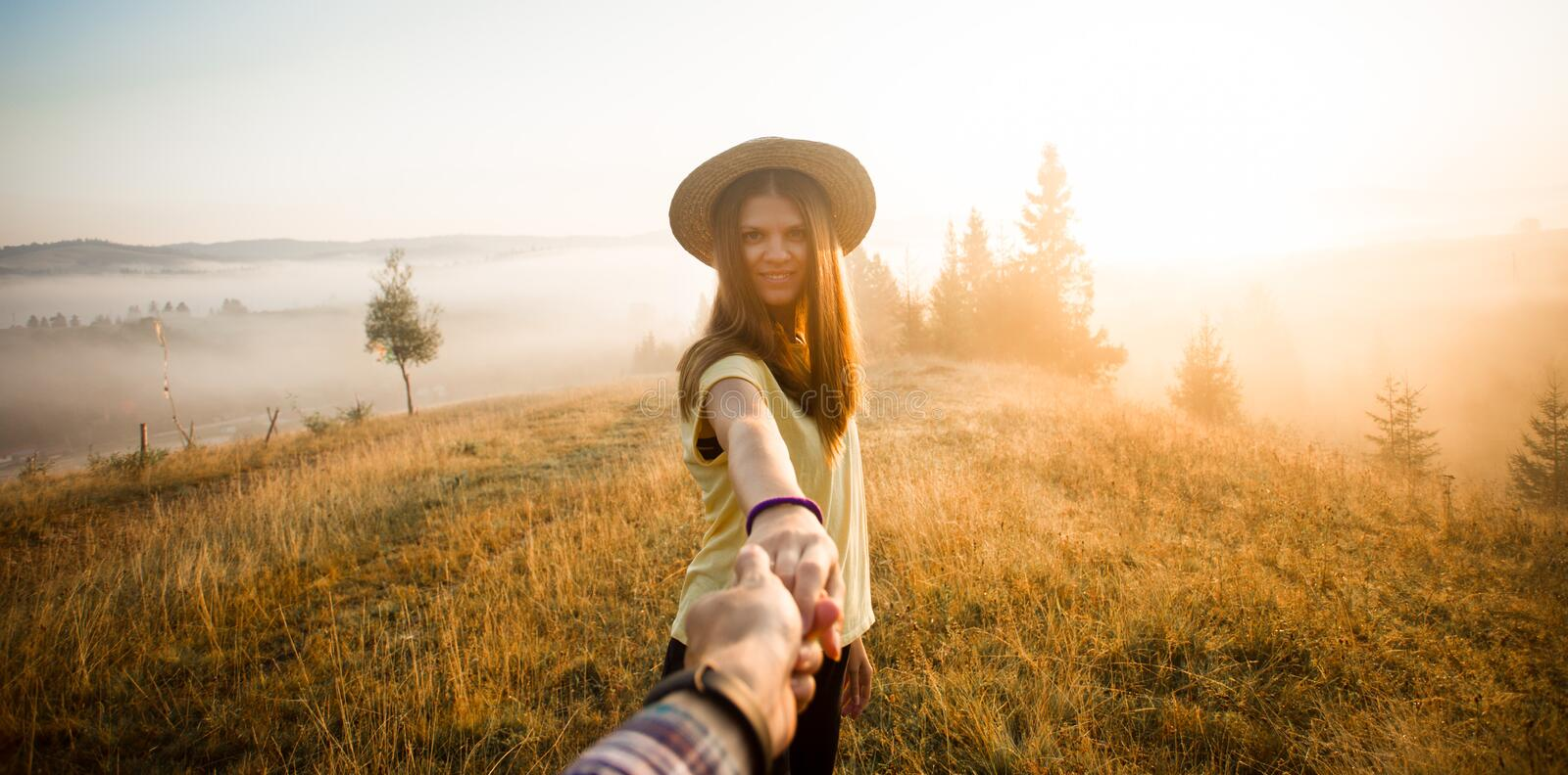 Follow me concept. Couple in love holding hands. Woman in yellow shirt and straw hat holding man by hand going to autumn forest stock photography