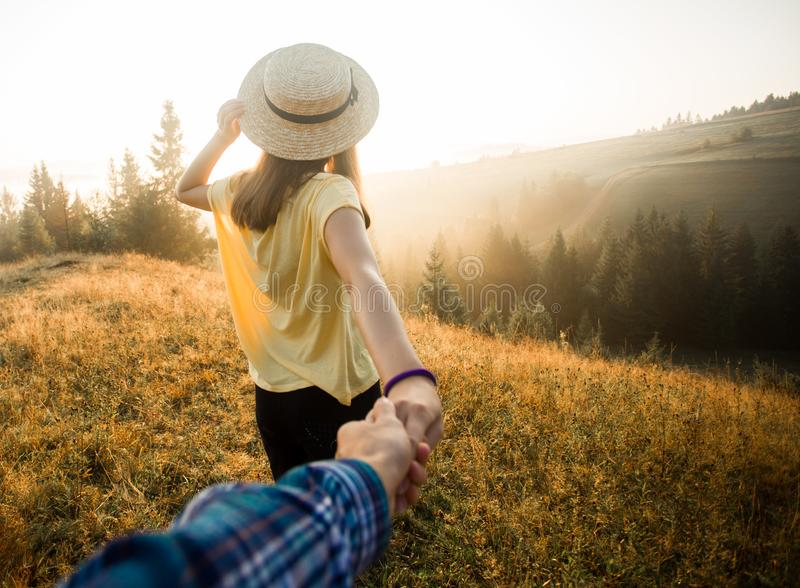 Follow me concept. Couple in love holding hands. Woman in yellow shirt and straw hat holding man by hand royalty free stock photography